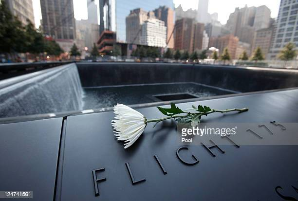 A flower sits on one of the panels containing names of the victims of the terrorist attacks on September 11 2001 at the 9/11 Memorial at the World...