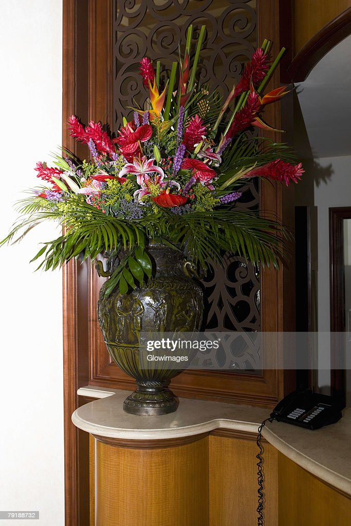 Flower vase and a telephone on a cabinet : Foto de stock