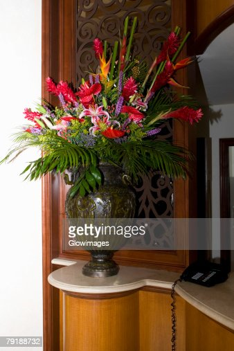 Flower vase and a telephone on a cabinet : Stock Photo