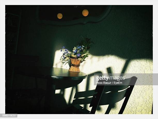 Flower Vase On Table Against Wall At Restaurant