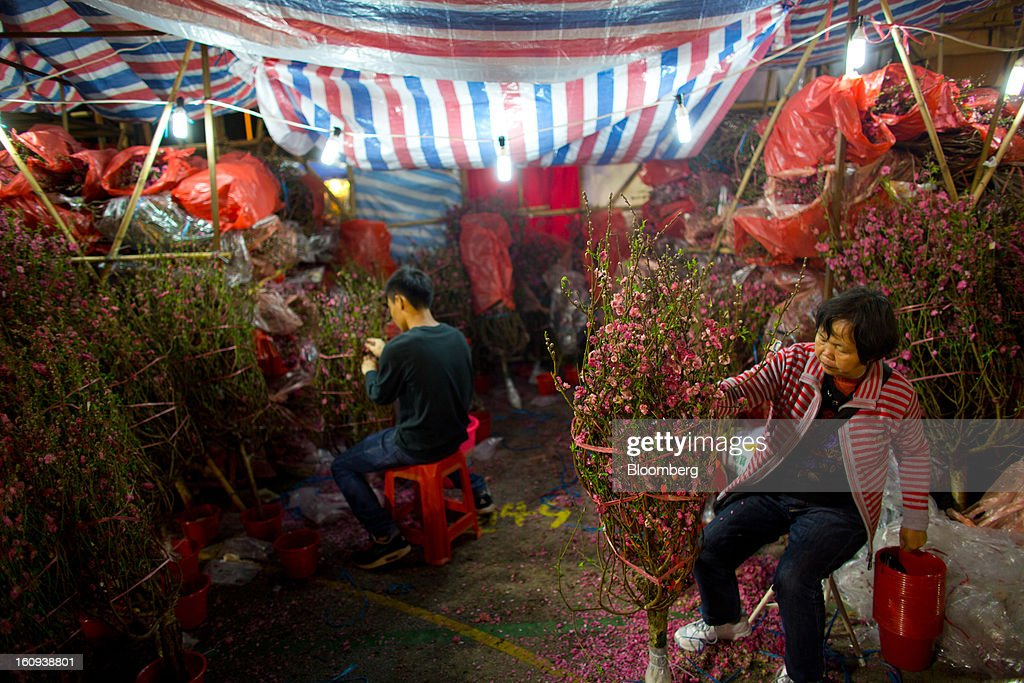 A flower vendor packages peach blossom branches for sale for the Lunar New Year in the Mongkok district of in Hong Kong, China, on Thursday, Feb. 7, 2013. Hong Kong's stock market will be shut for three days next week for the Lunar New Year holidays, while markets in mainland China will be closed for the whole week. Photographer: Lam Yik Fei/Bloomberg via Getty Images