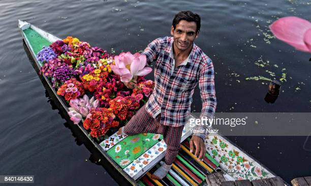 A flower vendor presents lotus flower to a Belgium tourist as other Kashmiri men remain busy in buying and selling vegetables at the floating...