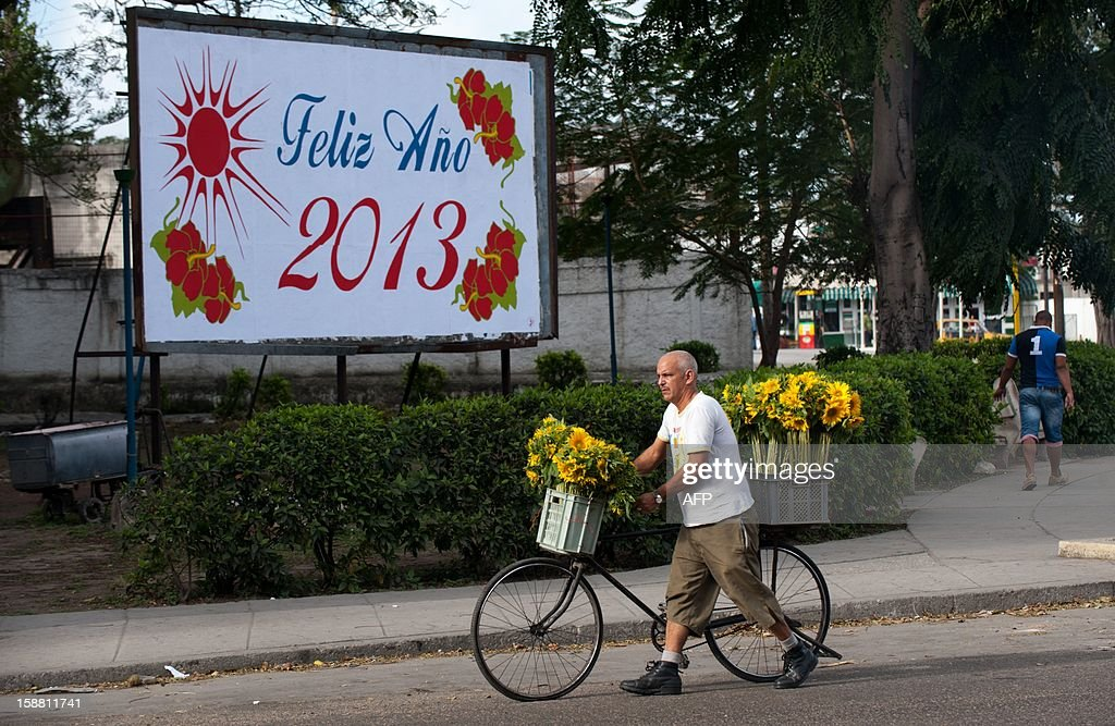 A flower vendro walks past a billboard with a New Year greeting in Havana on December 30, 2012.