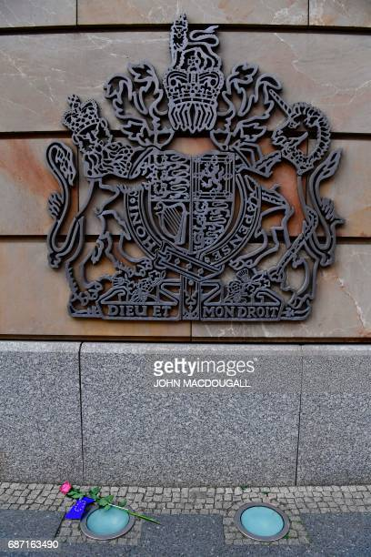 A flower with an EU flag attached to it lies beneath Britain's coat of arms at the British embassy in Berlin on May 23 following a terrorist attack...