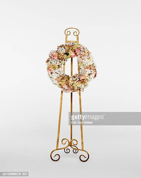 Flower wreath on stand on white background