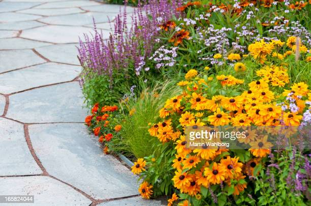 Flowerbed and paving stone slates in summer