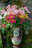 A bouquet of flowers in a ceramic vase near the old wall