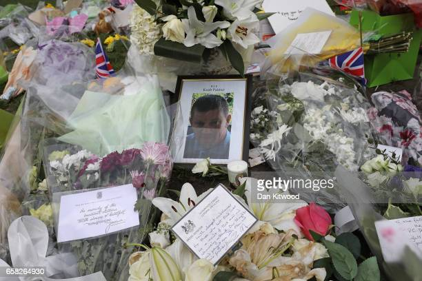 Flowers and a card signed by British Prime Minister Theresa May placed in memory of those who died in last weeks Westminster attack lie outside The...