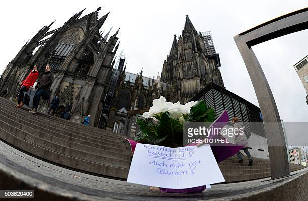 Flowers and a letter reading 'One doesn't beat people not even with flowers' are laid down in front of Cologne's landmark the Cologne Cathedral near...