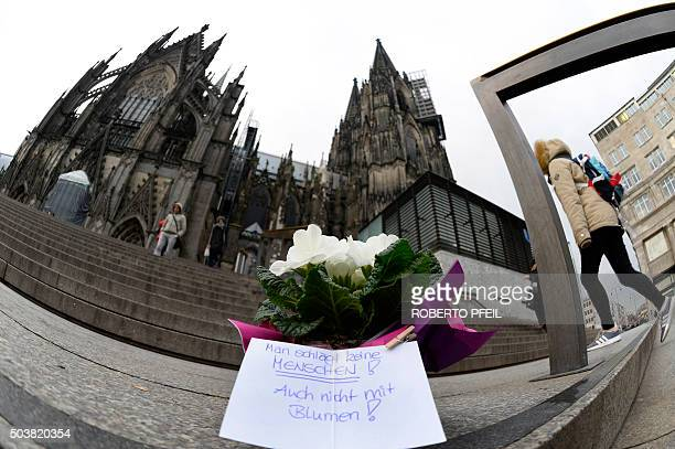 Flowers and a letter reading 'One doesn't beat women not even with flowers' are laid down in front of Cologne's landmark the Cologne Cathedral near...
