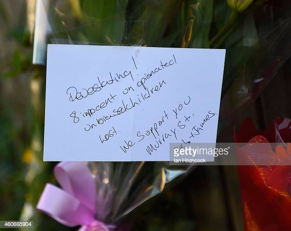 Flowers and a memorial note are seen laying up against a fence across the road from the scene of a multiple stabbing in the suburb of Manoora on...