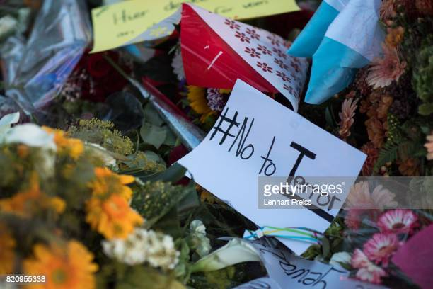 Flowers and a sign reading 'No to Terror' are seen at a memorial to commemorate the victims of the shooting spree that one year ago left ten people...