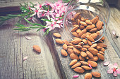 Flowers and almond nuts on a scattering of old wooden background, tinted