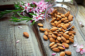 Flowers and almond nuts on a scattering of old wooden background.