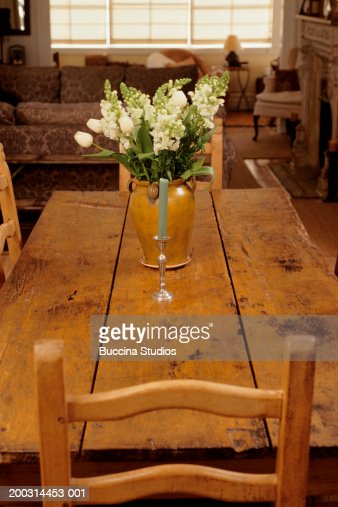 Flowers and candle in wooden table in dining room stock - Flowers for dining room table ...