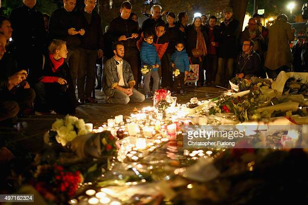 Flowers and candles are left on the pavement near the scene of yesterday's Bataclan Theatre terrorist attacks on November 14 2015 in Paris France At...