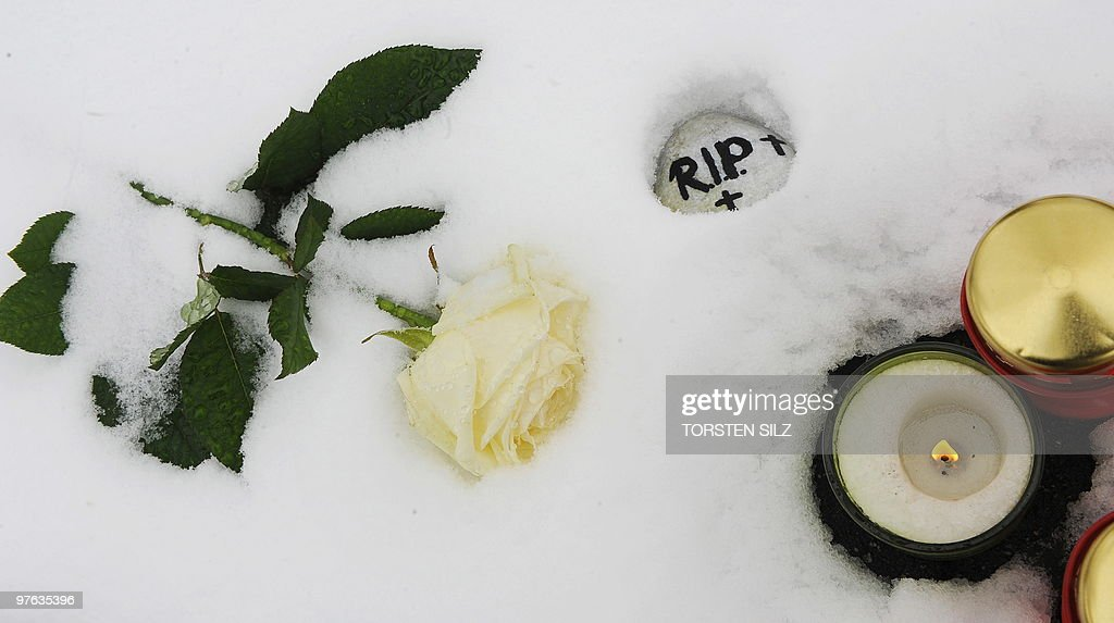 Flowers and candles have been left in the snow by people during a memorial service marking the first anniversary of the shooting at the Albertville secondary school in Winnenden, southern Germany on March 11, 2010. A year ago 17-year-old teenager Tim K. used his father's pistol to kill 12 people at the school and three others when he fled before killing himself.