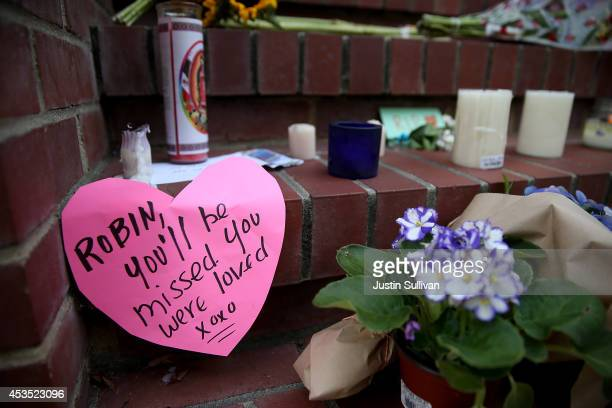 Flowers and pictures that are part of a growing memorial sit on the steps in front of the home where actor and comedian Robin Williams filmed the...
