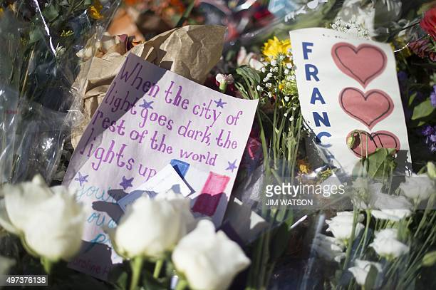 Flowers and signs are seen at a makeshift memorial outside the French Emabssy in Washington DC November 16 three days after a series of killings in...