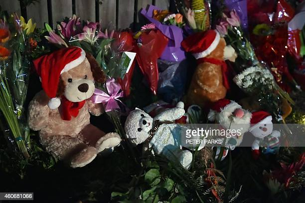 Flowers and stuffed toys are laid opposite the scene where eight children ranging from babies to teenagers were found dead in a house in the northern...