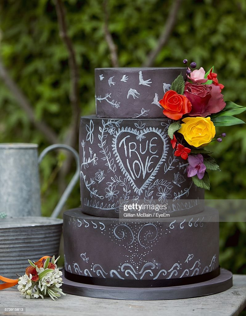 Flowers And Text On Layer Cake On Table Against Trees