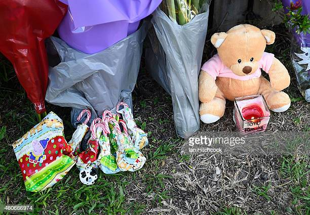 Flowers and toys are seen laying up against a fence across the road from the scene of a multiple stabbing in the suburb of Manoora on December 19...