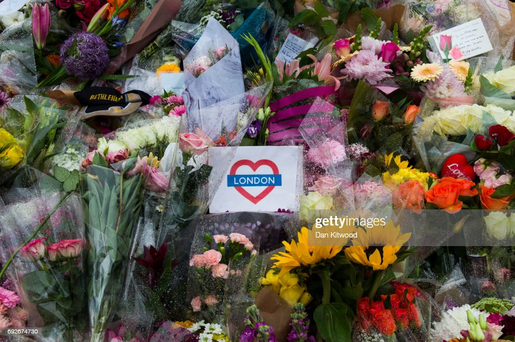 Flowers are laid on the south side of London Bridge close to Borough Market, in tribute to the victims of the June 3rd attacks, on June 5, 2017 in London, England. British police on Monday made several arrests in two dawn raids following the June 3 London attacks, claimed by the Islamic State group which left seven people dead.