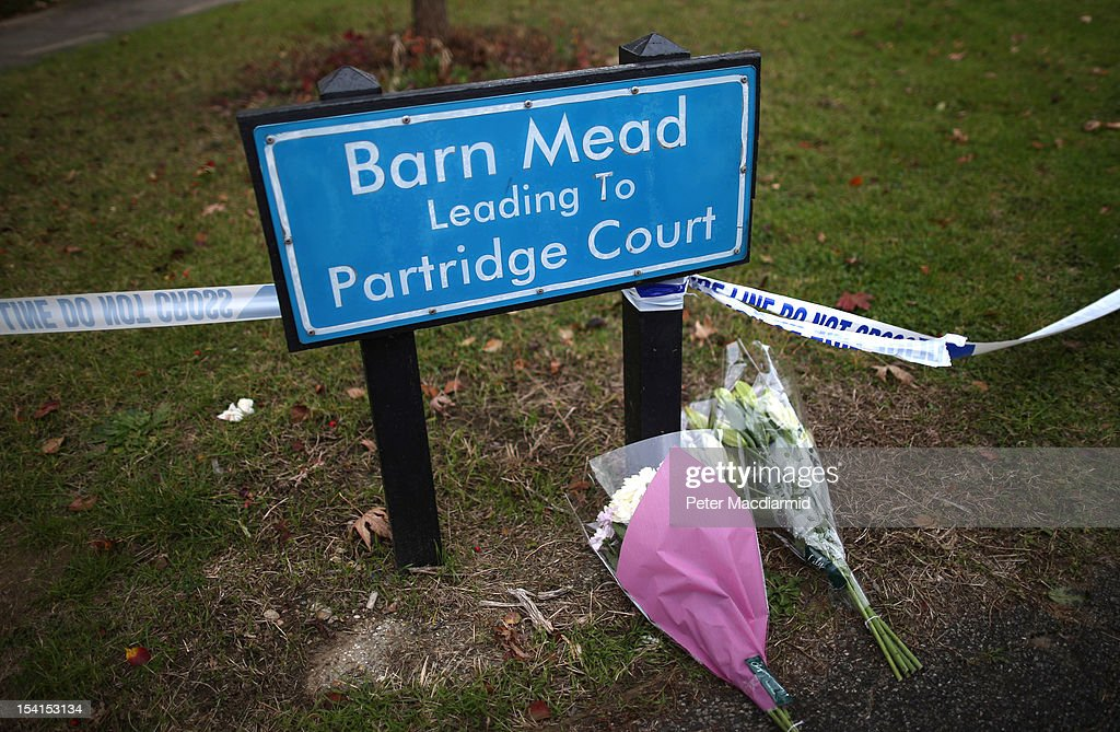 Flowers are left at a road sign denoting the name of the road where a house fire killed five people on October 15, 2012 in Harlow, England. A woman and four children have died and another three are in hospital after a fire in a house on an estate near Harlow in Essex.