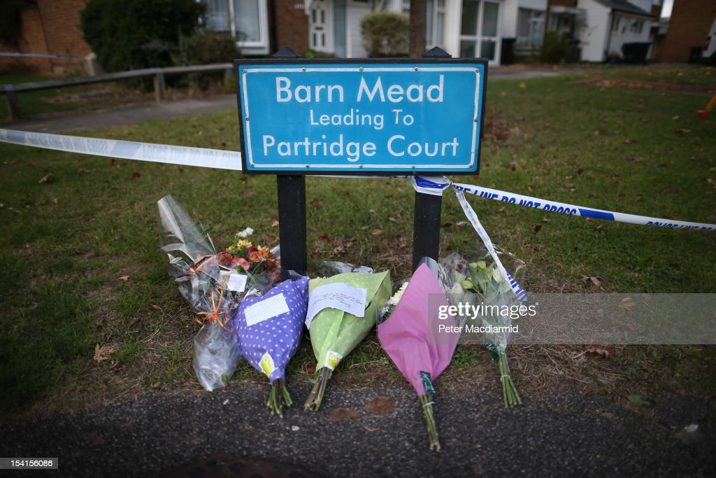 Flowers are left at a street sign denoting the name of the road where a house fire killed five people on October 15, 2012 in Harlow, England. A woman and four children have died and another three are in hospital after a fire in a house on an estate near Harlow in Essex.