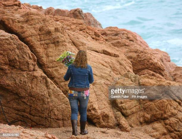 Flowers are left by a local English resident on rocks at the beach in Tossa de Mar in Spain where Symon Howlett and his son Jay drowned after being...