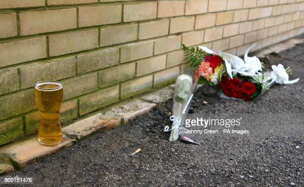 Flowers are left in an alleyway next to a pint of beer behind the beer garden of The New Inn public House on Myrtle Road in Sutton south London where...