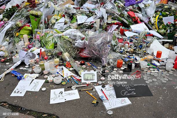 Flowers are left near the offices of French satirical magazine Charlie Hebdo on January 10 2015 in Paris France Four hostages and three suspects were...