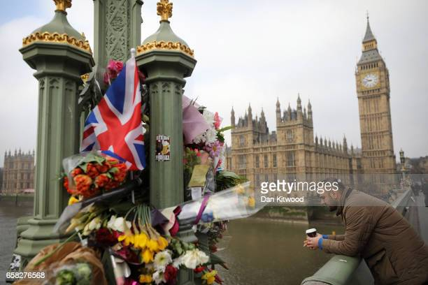 Flowers are left on Westminster Bridge by the Houses of Parliament in memory of those who died in last weeks Westminster terror attack on March 27...