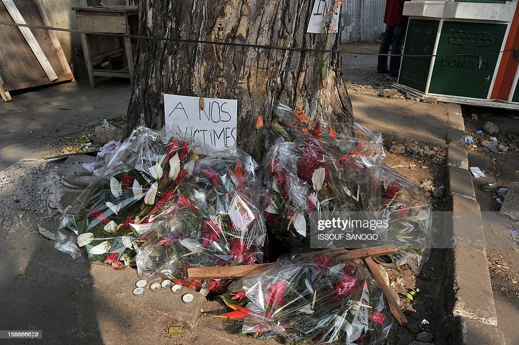 Flowers are pictured on January 2, 2013 at a tree in the street of Abidjian where at least 60 persons died in a stampede among crowds gathered for celebratory New Year's Eve fireworks that also left dozens injured. Ivory Coast began today three days of national mourning.