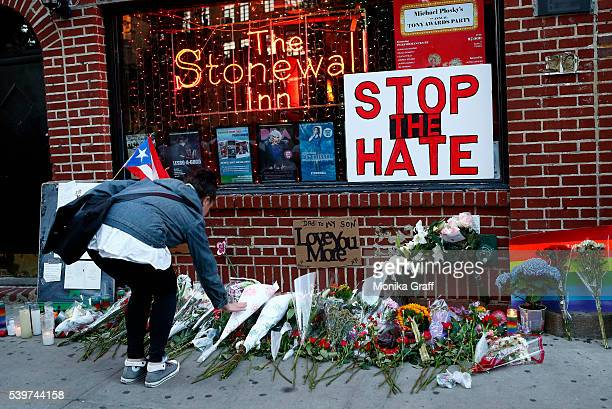 Flowers are placed at a makeshift memorial in front of the Stonewall Inn where a vigil was held following the massacre that occurred at a gay Orlando...