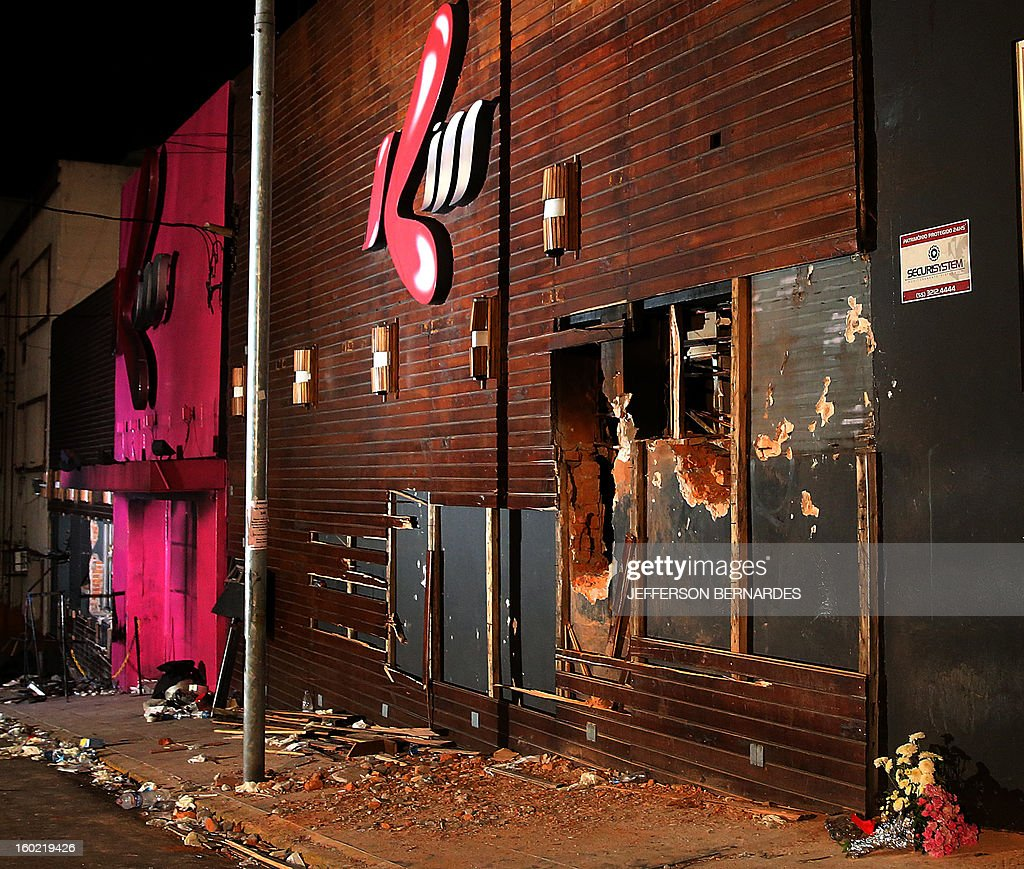 Flowers are placed at the doors of the Kiss night club fire after fire ripped through the premises, on January 27, 2013 in Santa Maria. Brazilians were mourning the victims of a nightclub blaze in a small college town that left more than 230 people dead and over 100 injured, with many still fighting for their lives.