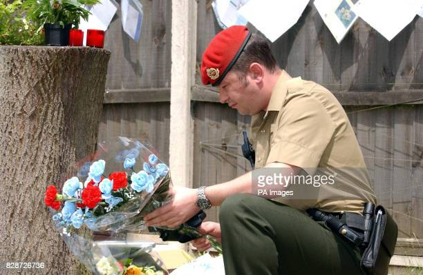 Flowers are placed by Cpl Mark Brown of 156 Provost Company at the memorial setup at the military police station garden Colchester The six victims...