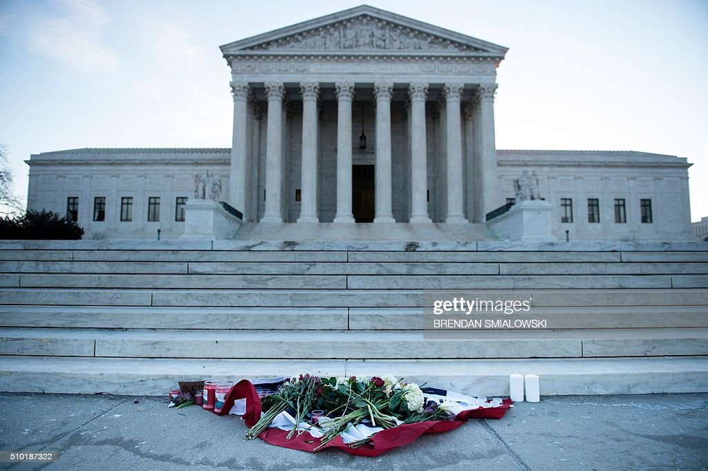 Flowers are placed in front of the US Supreme Court on February 14, 2016 in Washington. Justice Antonin Scalia, a towering conservative voice on the US Supreme Court, has died at the age of 79, triggering a political showdown over his succession in the run-up to the presidential election. President Barack Obama ordered flags to fly at half-staff across the United States until the long-serving justice, first appointed by Ronald Reagan in 1986, is laid to rest. / AFP / Brendan Smialowski