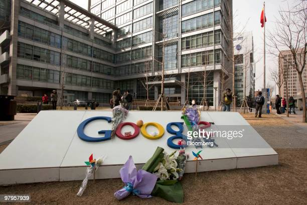 Flowers are placed on a sign outside the Google Inc office in Beijing China on Tuesday March 23 2010 Google Inc following through on a pledge to stop...