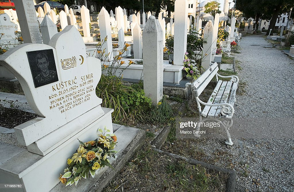 Flowers are placed on graves in a cemetery where fvictims of the 1993 siege rest as the city of Mostar remembers the 1993 conflict on June 28, 2013 in Mostar, Bosnia and Herzegovina. The Siege of Mostar peaked in 1993 during the Croat-Bosniak conflict lasting eighteen months as fighting took place as Bosnia and Herzegovina declared independence from Yugoslavia. The city was divided in half between the two battling armies. Mostar, dating back over four hundred years, was mostly destroyed through the fighting. Although reconstruction has slowly commenced in the last decades, evidence of the war remains in bullet ravaged buildings still standing throughout the city.