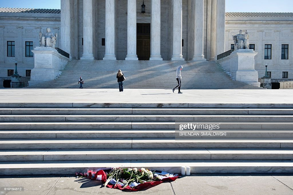 Flowers are seen as people visit the US Supreme Court February 14, 2016 in Washington. Justice Antonin Scalia, a towering conservative voice on the US Supreme Court, has died at the age of 79, triggering a political showdown over his succession in the run-up to the presidential election. President Barack Obama ordered flags to fly at half-staff across the United States until the long-serving justice, first appointed by Ronald Reagan in 1986, is laid to rest. / AFP / Brendan Smialowski