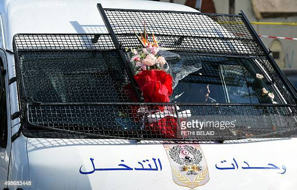 Flowers are seen on a police vehicle near the wreckage of a bus the day after a bomb attack on the vehicle which was transporting Tunisia's...