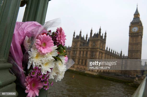 Flowers are seen on Westminster Bridge one of the scenes of the March 22 terror attack close to the Houses of Parliament in central London on March...