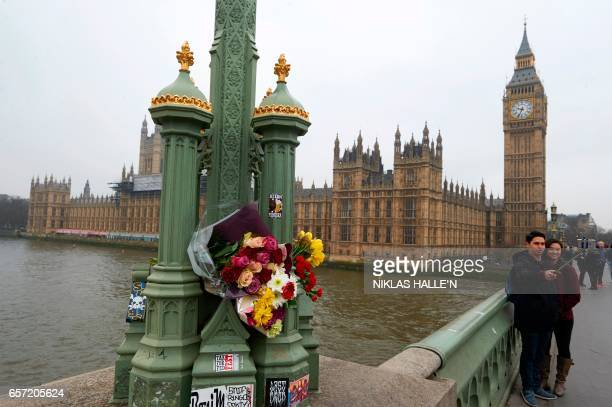 Flowers are seen on Westminster Bridge one of the scenes of the March 22 terror attack as tourists take a selfie photo in from of the Houses of...