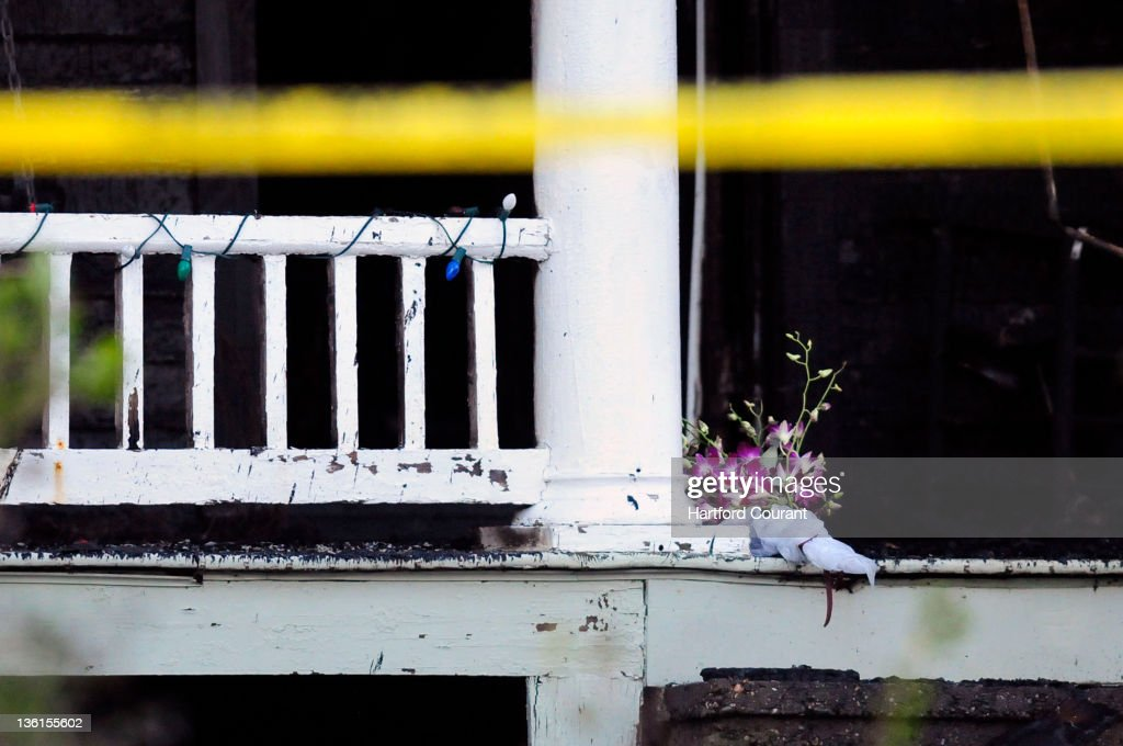 Flowers brought by a neighbor lay on the porch where holiday lights remain at the house in Stamford Connecticut where an earlymorning fire on...
