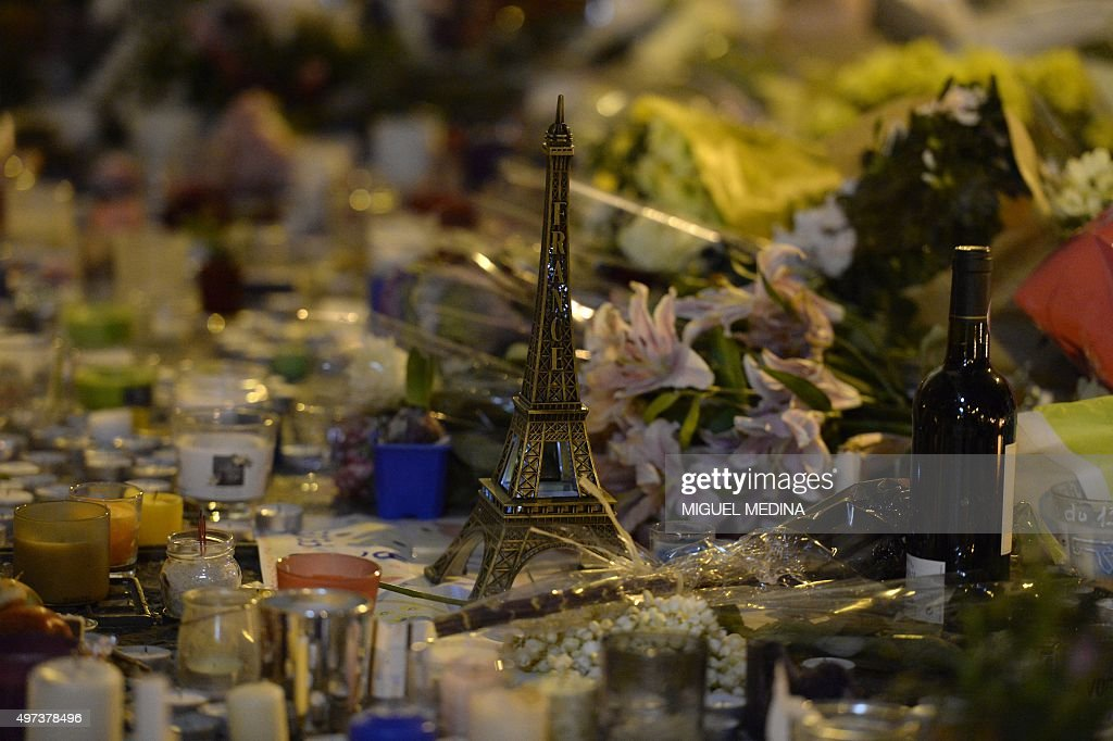 Flowers candles an Eiffel tower model and a red wine bottle are seen outside Le Carillon cafe on November 16 2015 at the corner of Rue Bichat and...