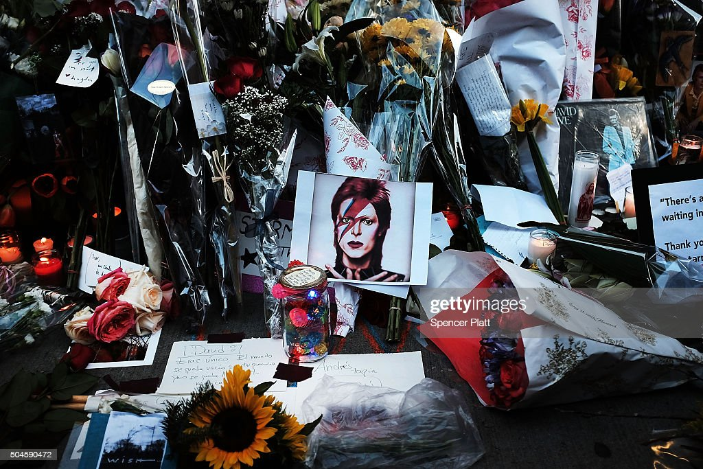 Flowers candles and pictures sit at a memorial outside of the late musician and performer David Bowie's apartment that he shared with his wife on...