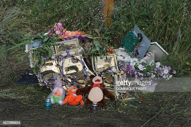 Flowers candles and plush toys are left by electronic wreckage at the site of the crash of a Malaysia Airlines plane carrying 298 people from...