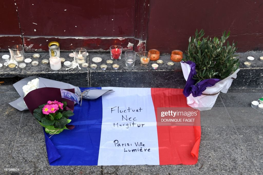 Flowers candles and the French national flag with the Latin 'Tossed but not sunk' the motto of Paris written on it is laid outside of the Carillon...