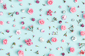 Flowers composition. Pattern made of pink flowers on pastel blue background. Flat lay, top view